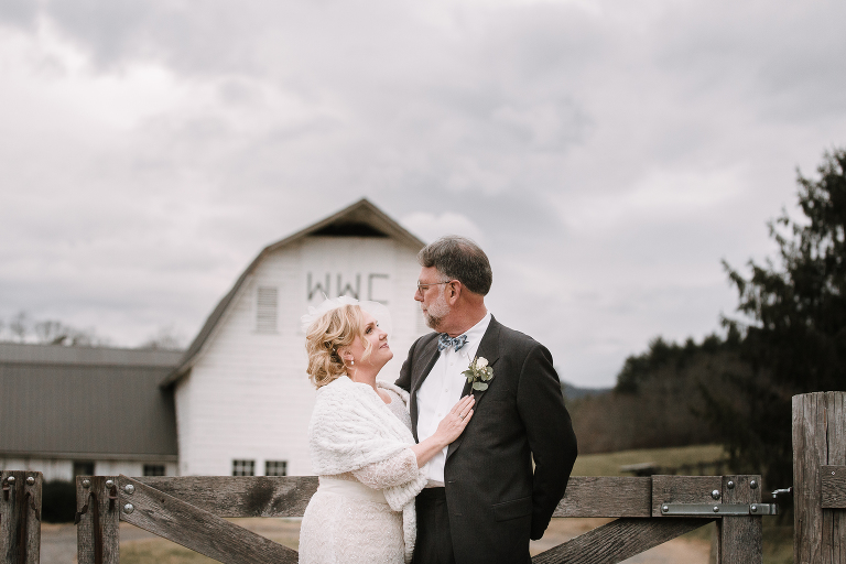 Bridge and Groom standing in front of barn at Warren Wilson College in Swannanoa